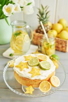Nackter kuchen mit zitronen und limetten, limonade, früchten und tulpenblüten