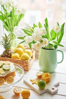 Nackter kuchen mit zitronen und limetten, süßen macarons und blumen in der vase