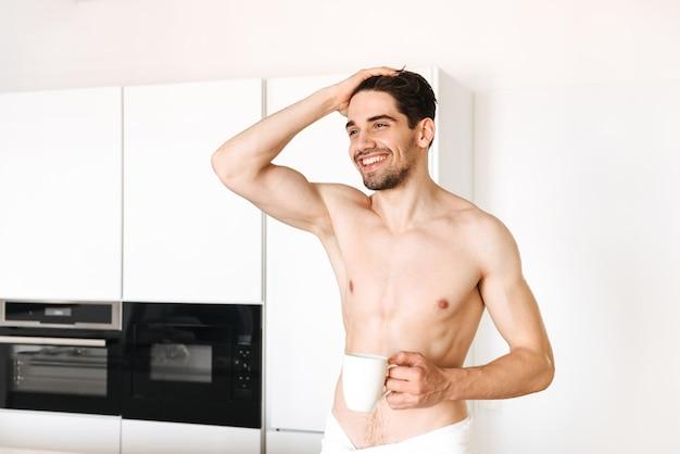 Nackter mann, der drinnen an der küche mit handtuch steht