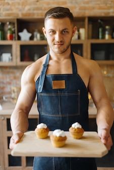 Nackter mann in der schürze hält tablett mit süßem dessert auf der küche. nackte männliche person, die frühstück zu hause vorbereitet, essenszubereitung ohne kleidung