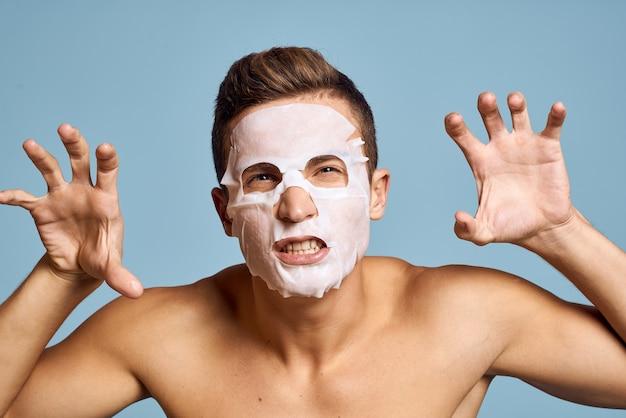 Nackter mann mit weißer nährmaske auf gesicht auf blau