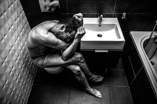 Nackter mann sitzt in der alten stadttoilette. person fühlt schrecklichen emotionalen schmerz und hilflosigkeit.