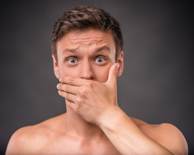 Nackter mann steht und deckt seinen mund mit der hand.