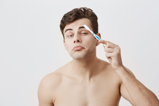 Nackter muskulöser kerl mit trendiger frisur, gesunder haut, gesicht machen, spaß drinnen haben, augenbrauen mit zahnbürste kämmen. attraktiver mann mit ansprechendem aussehen posiert.