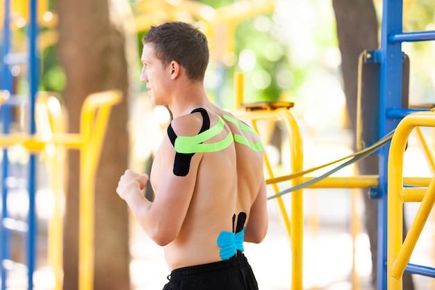 Nackter muskulöser mann, der im park auf dem spielplatz trainiert
