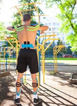 Nackter muskulöser mann trainiert mit fitnessseil am sportplatz. rückansicht eines jungen, nicht erkennbaren bodybuilders mit elastischer kinesiologie, die beim körpertraining im freien aufnimmt. rehabilitationskonzept.