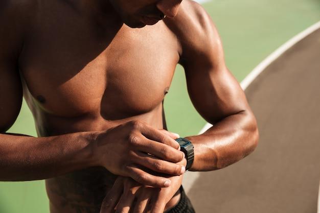 Nackter oberkörper afroamerikanischer muskulöser sportmann, der zeit auf armbanduhr nach dem training prüft