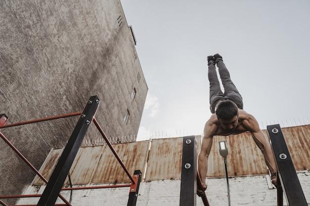 Nackter oberkörper athlet, der calisthenics übt. junger mann, der handstandübung auf parallelstangen tut.