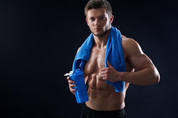 Nackter oberkörper athletischer junger mann mit einem handtuch und einer wasserflasche nach