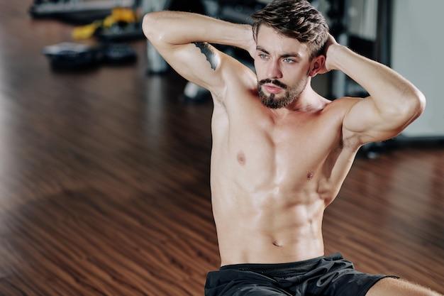 Nackter oberkörper, attraktiver, fitter junger mann, der im fitnessstudio crunches macht