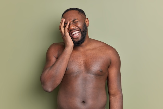 Nackter oberkörper bärtiger mann lässt gesichtspalme glücklich über etwas positives lachen hat weiße perfekte zähne steht im studio gegen dunkelgrüne wand