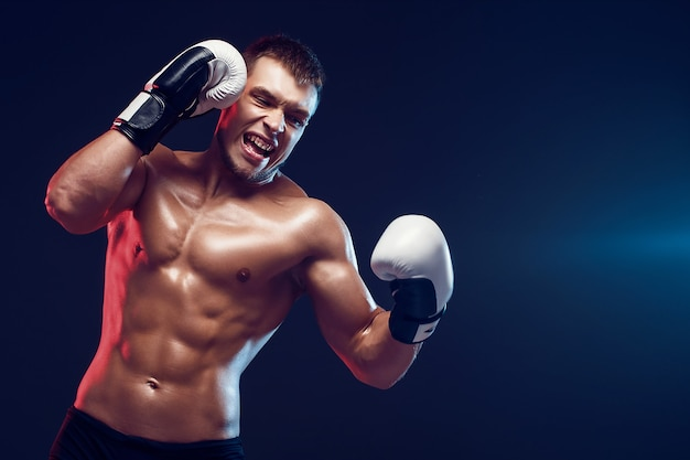Nackter oberkörper boxer mit handschuhen auf dunklem hintergrund. isolieren