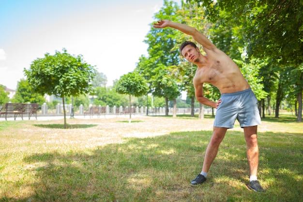 Nackter oberkörper, der übung im park macht