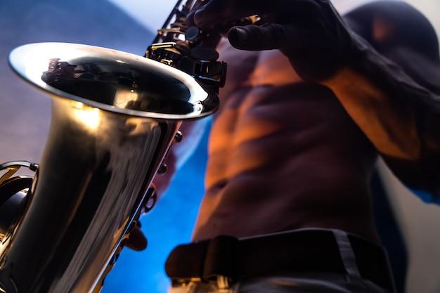 Nackter oberkörper des muskulösen mannes, der auf saxophon mit geräuchertem buntem hintergrund spielt