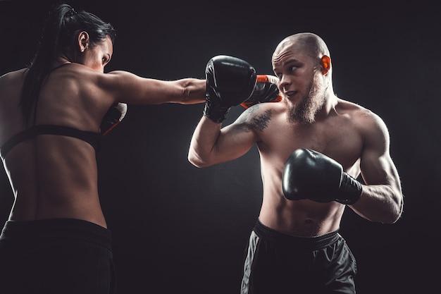 Nackter oberkörper frau, die mit trainer am box- und selbstverteidigungsunterricht trainiert weiblicher und männlicher kampf