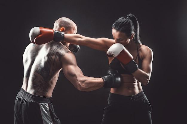 Nackter oberkörper frau, die mit trainer an der box- und selbstverteidigungsstunde, studio, dunkler raum ausübt