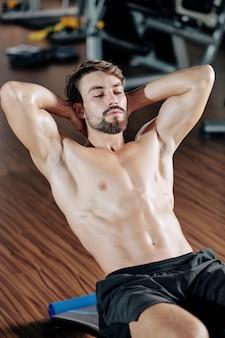 Nackter oberkörper hübscher passender junger mann, der knirschen auf bank im fitnessstudio tut