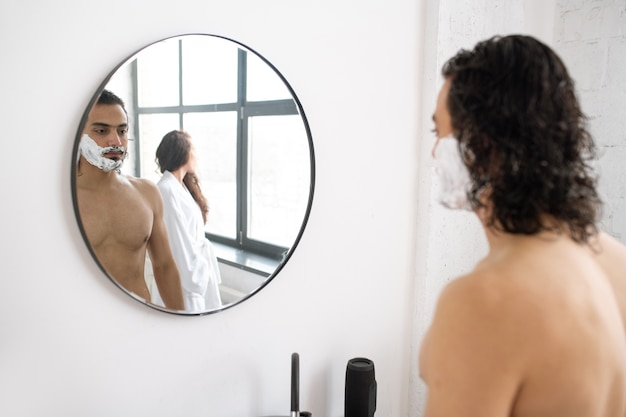 Nackter oberkörper junger mann mit rasierschaum auf seinem bart, der vor spiegel mit spiegelung og seiner freundin steht, die weißen bademantel trägt