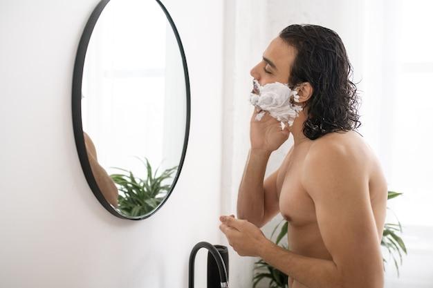 Nackter oberkörper junger muskulöser mann, der rasierschaum auf gesicht beim betrachten im spiegel im badezimmer anwendet