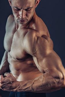 Nackter oberkörper männlicher bodybuilder mit muskulösem aufbau starker bauchmuskeln, die einen schuss eines gesunden muskulösen jungen mannes zeigen, der perfekt zu sixpack passt