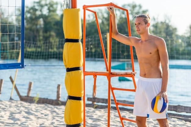 Nackter oberkörper männlicher volleyballspieler am strand, der ball hält