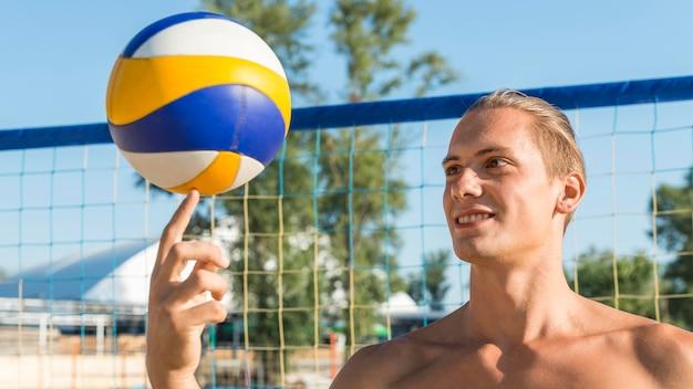 Nackter oberkörper männlicher volleyballspieler, der ball mit finger hält