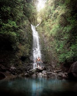 Nackter oberkörper mann, der auf felsen nahe einem schönen wasserfall mit einem see und grün steht