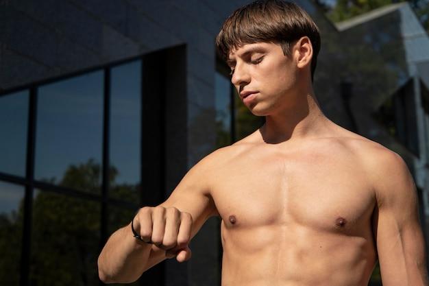 Nackter oberkörper mann, der sein fitnessband beim ausarbeiten im freien betrachtet