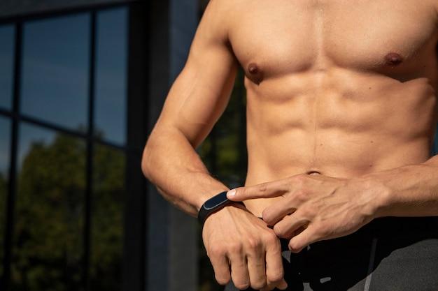 Nackter oberkörper mann mit fitnessband im freien