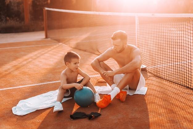 Nackter oberkörper vater und sohn sitzen auf handtüchern auf dem platz und ruhen sich vom kickball aus. sommerzeit am morgen.
