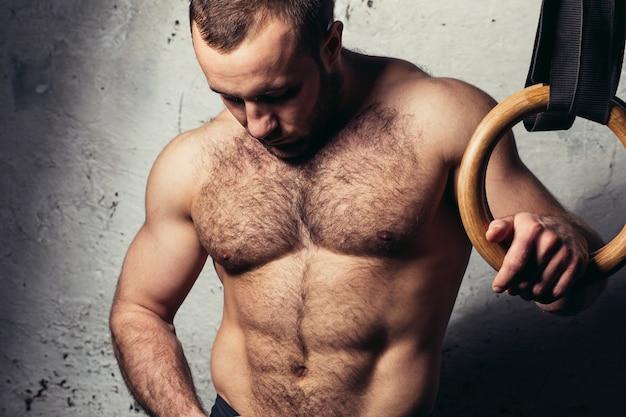 Nackter torso des jungen muskulösen attraktiven mannes, der gegen gymnastikringe aufwirft