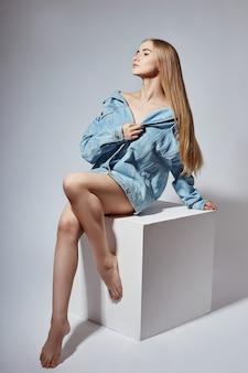 Nacktes blondes mädchen der mode sitzt auf weißem würfel