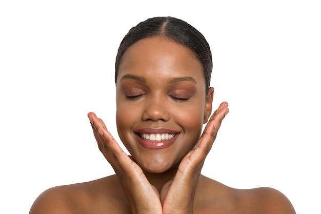Nacktes junges ethnisches model mit perfekter haut und lipgloss, das fröhlich mit geschlossenen augen an einer weißen wand lächelt