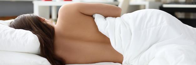 Nacktes mädchen schläft zu hause unter weißer decke