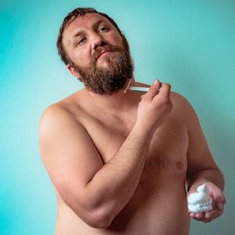 Nacktes männliches model rasiert sich seinen eigenen bart