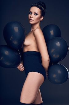 Nacktes modellmädchen der schönen mode mit schwarzen luftballons, die lokalisiert auf weißem hintergrund aufwerfen.