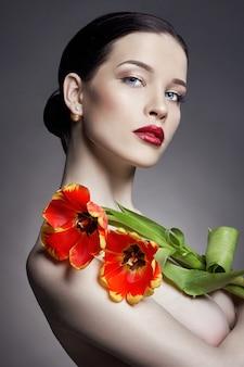Nacktes nacktes mädchen mit tulpen blüht in der hand
