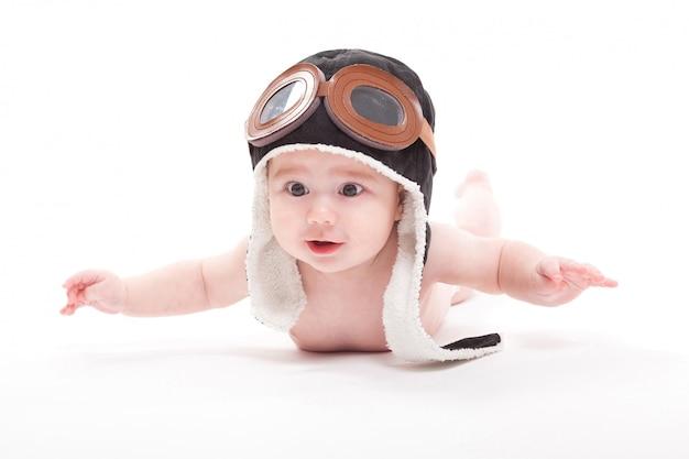 Nacktes nettes lächelndes baby in der kappe des piloten fliegt