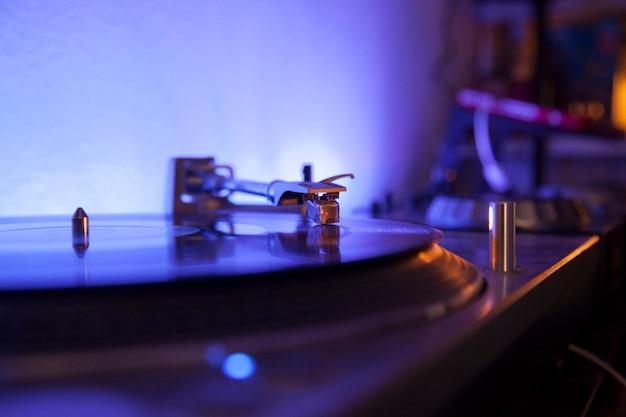 Nadel spielt vinilo-schallplatte auf einem blauen led-licht