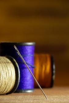 Nadel und threads auf holztisch.