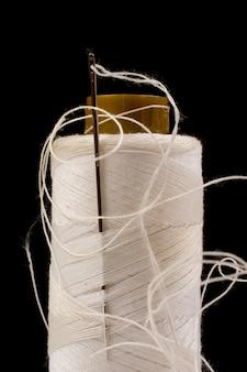 Nadel und weiße baumwolle, verwickeltes garn auf rolle zum nähen. faden für die textil- und textilindustrie. schwarzer hintergrund