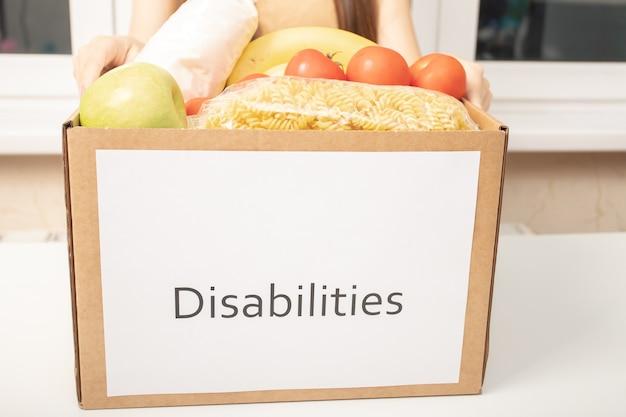 Nächstenliebe und hilfe für menschen in not. frauenhände halten eine schachtel mit lebensmitteln für behinderte