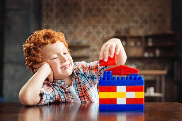 Nächster großer architekt. entzückender kleiner junge, der seine aufmerksamkeit auf eine hand legt und breit grinst, während er an einem tisch sitzt und es genießt, mit einem baukasten zu spielen.