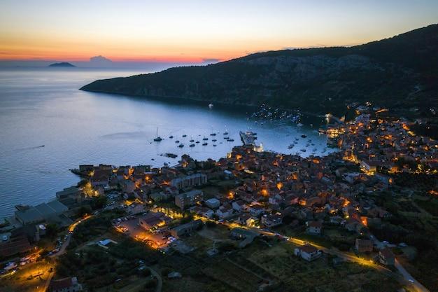 Nächtliche luftaufnahme der küstenstadt komiza auf der insel vis, kroatien in dalmatien von der drohne bei nacht. touristenziel im mittelmeer. kleine stadt mit straßenlaternen im sommer bei sonnenuntergang.