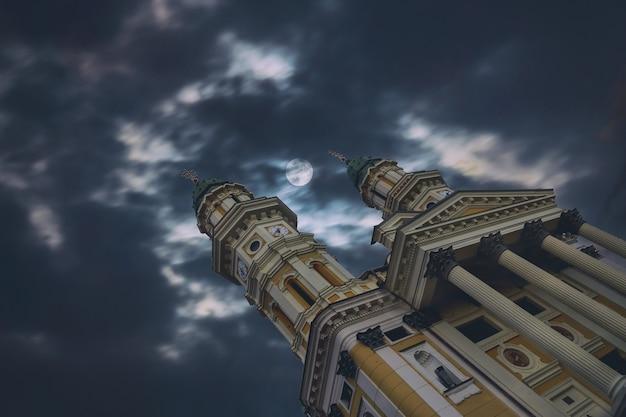 Nächtlicher himmel der griechischen katholischen kathedralen-kirche mit mond und wolken in uzhhorod-stadt ukraine