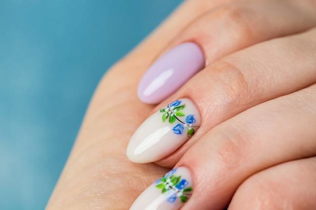Nägel design. hände mit hellem flieder und weißer maniküre mit frühlingsblumen. nahaufnahme der weiblichen hände. kunstnagel.