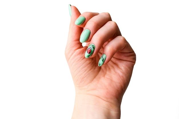 Nägel design. hände mit hellgrüner maniküre mit blumen. nahaufnahme der weiblichen hände. kunstnagel.
