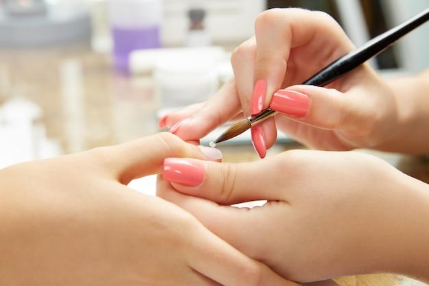 Nägel, die frau mit bürste im nagelstudio malen