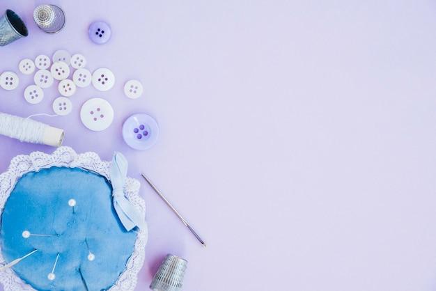 Nähartikel mit nadelkissen; fingerhut; nadel; spule und knopf auf purpurrotem hintergrund
