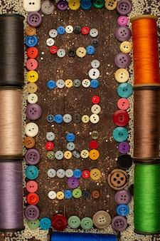 Nähen von fäden zusammen mit bunten plastikknöpfen, die hallo wort auf einem braunen rustikalen tisch bilden